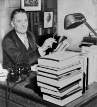 literary agent at desk with piles of books