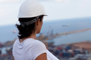 woman in white hard hat looking at harbor