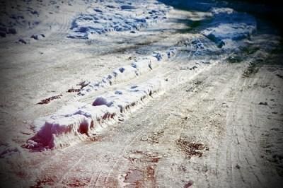 snowy road with gray slush and tire tracks