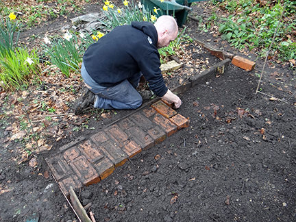 Justin laying a path with salvaged bricks on the allotment