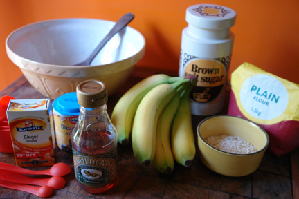 ingredients to make banana ginger parkin sitting on a vintage wooden butchers block