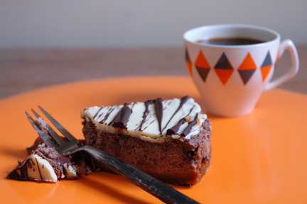 slice of baked chocolate and ginger cheesecake with small cup of black coffee
