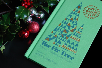 """The Fir Tree"" book illustrated by Sanna Annuka with Christmas baubles and sprig of holly with red berries"