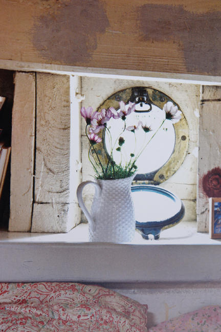 white vintage pottery jug of flowers in front of a porthole