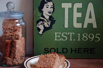 glass jar full of flapjack pieces, plate with two flapjack pieces and green painted tin retro tea advertising sign
