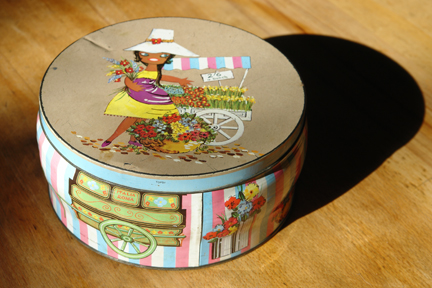 vintage biscuit tin with illustration by Lefor-Openo of a flower seller girl with her market stall