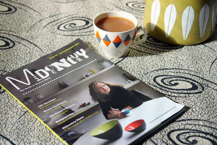 image of the front cover of the 1st edition of Midcentury Magazine pictured with a vintage Cathrineholm kettle and vintage harlequin china cup & saucer all on a piece of 1950s monochrome Crabtree fabric with milky way pattern
