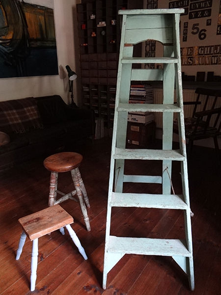 two vintage wooden stools with painted legs and a set of green-painted ladders