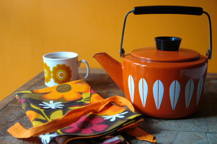 vintage orange enamel Cathrineholm &quot;Lotus&quot; kettle with vintage orange floral patterned apron and orange floral print Staffordshire Pottery mug