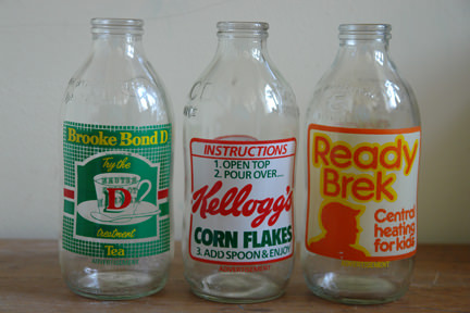 three vintage milk bottles advertising Brooke Bond Tea, Ready Brek and Kellogg's Corn Flakes