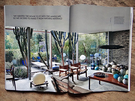 May 2014 Elle Decoration magazine double page spread showing sitting room with large glass floor to ceiling windows looking out to the garden