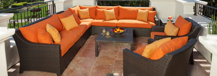 set of rattan outdoor furniture with orange cushion covers