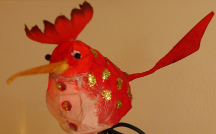 Detail of a colourful tissue paper bird, one of six along a string of fairy lights