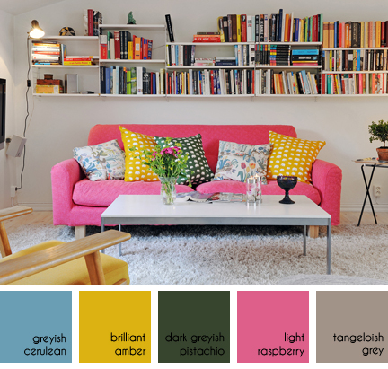 pink sofa with colourful cushions beneath a wall of bookshelves