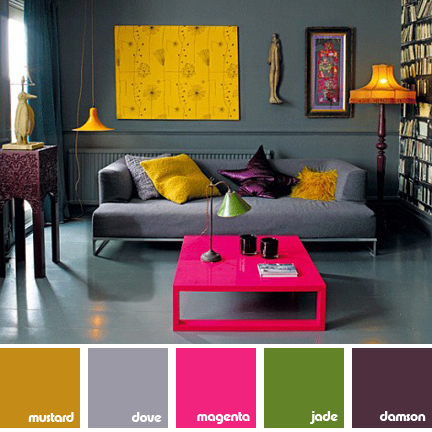 sitting room with grey floor, walls and sofa; magenta coffee table, yellowlampshades and cushions green table lamp and purple cushion
