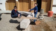 The boys playing with balancing against concrete paving stones we made
