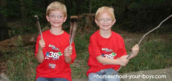 Boys with feathers and a stick