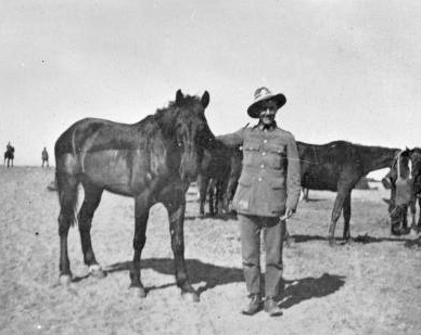 """Unidentified soldier of the Canterbury Mounted Rifles (34th Reinforcements) holding a horse named """"Dick"""" in the first half of 1919. © Alexander Turnbull Library"""