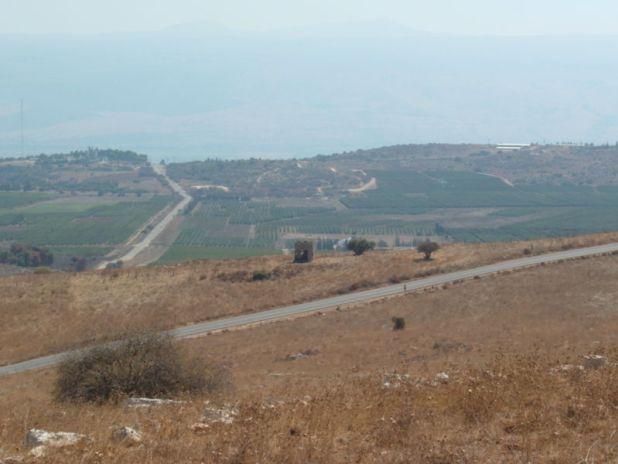"""כביש הצפון בין צומת כ""""ח וסאסא. לצד הכביש – שרידי פילבוקס הרוס. האזור המעובד הוא בקעת קדש, וברקע נראים עמק החולה והגולן"""