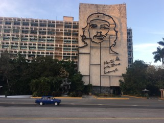 Che sculpture on the side of building with small soviet car