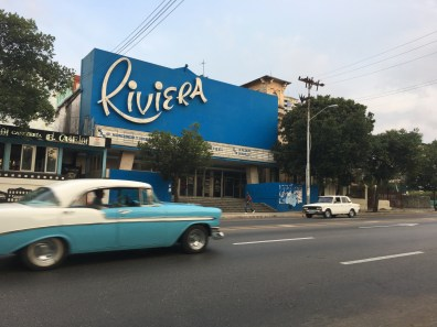 Blue 1950's cinema 'Riviera' with light blue 1950's Amercan car in front