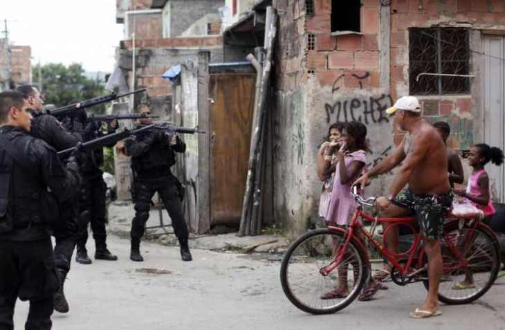 in-the-run-up-to-junes-world-cup-brazil-deployed-troops-to-the-slums-of-rio-de-janeiro-to-rid-them-of-violent-crime-drugs-and-gangs-the-photo-shows-residents-reacting-to-policemen-taking-up-position-before--75