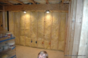 How Do You Finish a Basement. Framed wall with insulation and lighting.