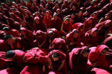 Tibetan monks sit as they wait for the body of Jamphel Yeshi inside the Tsuglagkhang temple in Dharamsala