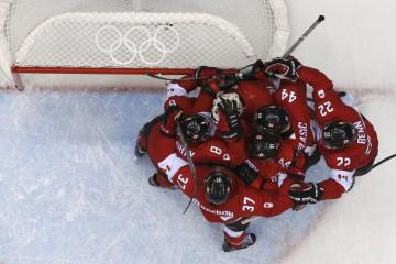 Canada's players congratulate goalie Price after Canada defeated Team USA in their men's ice hockey semi-final game at the Sochi 2014 Winter Olympic Games