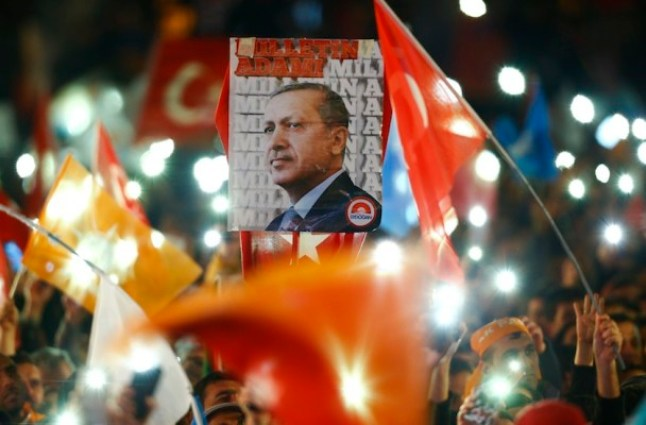 People wave flags and hold a portrait of Turkish President Tayyip Erdogan as they wait for the arrival of Prime Minister Ahmet Davutoglu in Ankara, Turkey November 2, 2015. Davutoglu described the outcome of a general election which swept his AK Party back to a parliamentary majority on Sunday as a victory for democracy. REUTERS/Umit Bektas - RTX1UASN