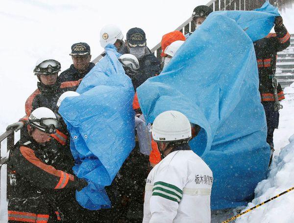 Los rescatistas con los cuerpos de algunas víctimas de la avalancha ocurrida en la ciudad de Nasu, al norte de Tokyo (Reuters)