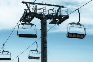 Empty chairs on a sky lift.