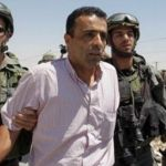 A Palestinian protester is detained during a demonstration against Israel.