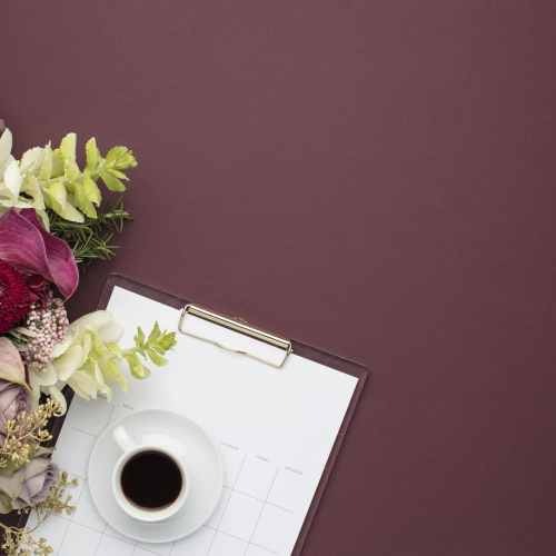 Coffee, Notepad, Flowers Flatlay on Purple Background