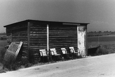 Old hut with four empty chairs to the front