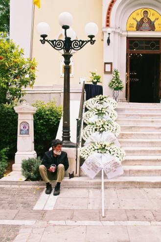 A beggar sitting next to funeral wreaths.