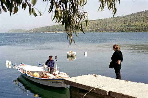 A port scene of a woman speaking with a fisherman.