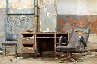 An office desk with chairs in decaying condition