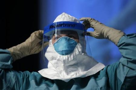 Smith demonstrates putting on personal protective equipment during an Ebola educational session for healthcare workers at the Jacob Javits Convention center in New York