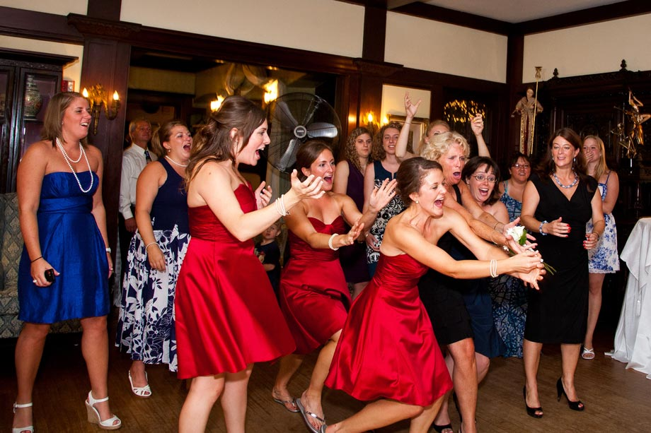 bridesmaids in red catching bouquet