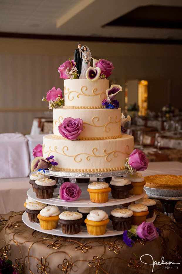 round white flowered wedding cake with cupcakes at the base
