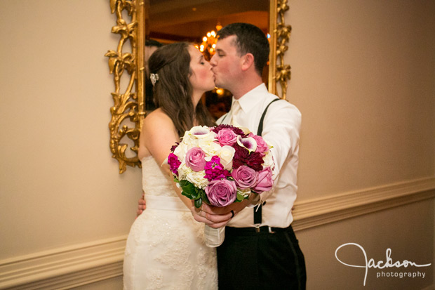 bride and groom kissing while holding flower bouquet