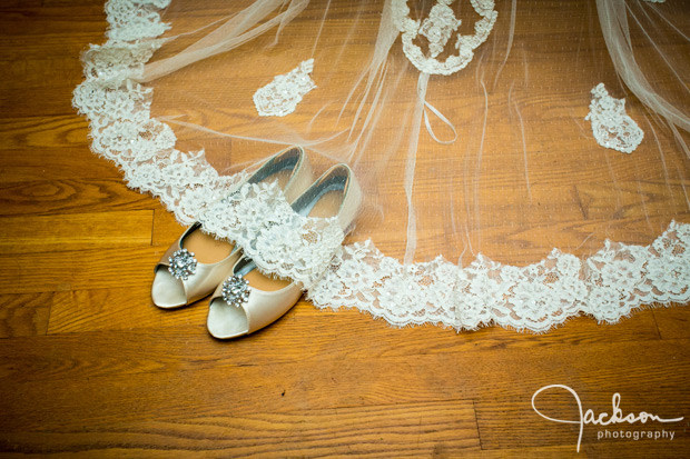 bride's white silver shoes with veil over them