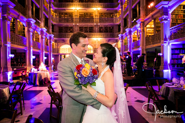 bride and groom at wedding reception lit by purple lights