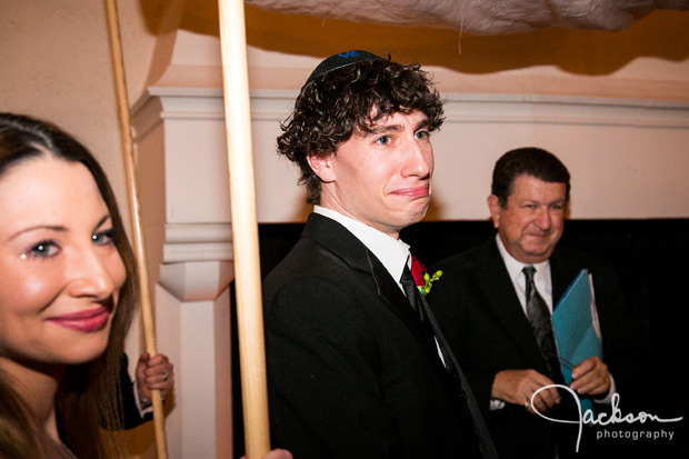 groom emotionally looking at bride walking down aisle