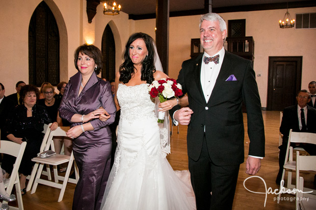 bride walking down aisle with mother and father