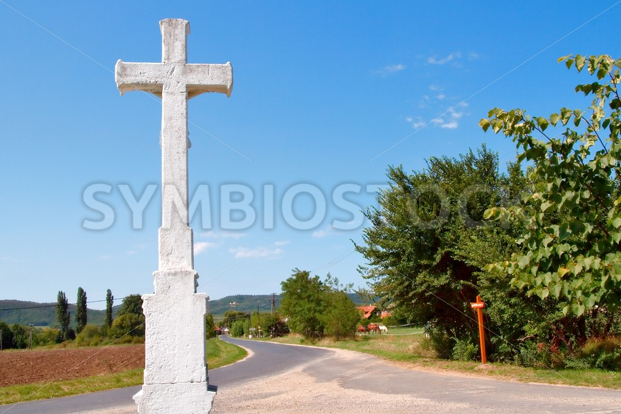 Village scene with crucifix - Jan Brons Stock Images