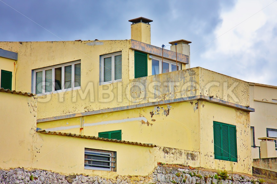 Yellow worn out concrete house - Jan Brons Stock Images