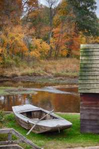 A small boat with the fall colors of a New England fall foliage season at hand.