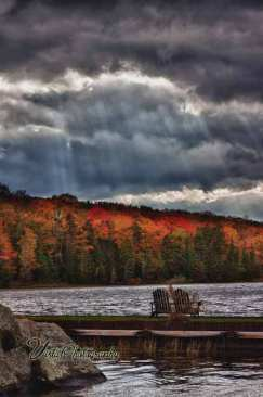 Groton State park with fall colors spotlighted by sun through clouds